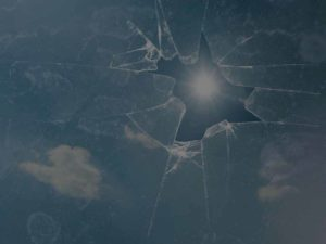picture of broken glass with the sun shining through the hole in the glass