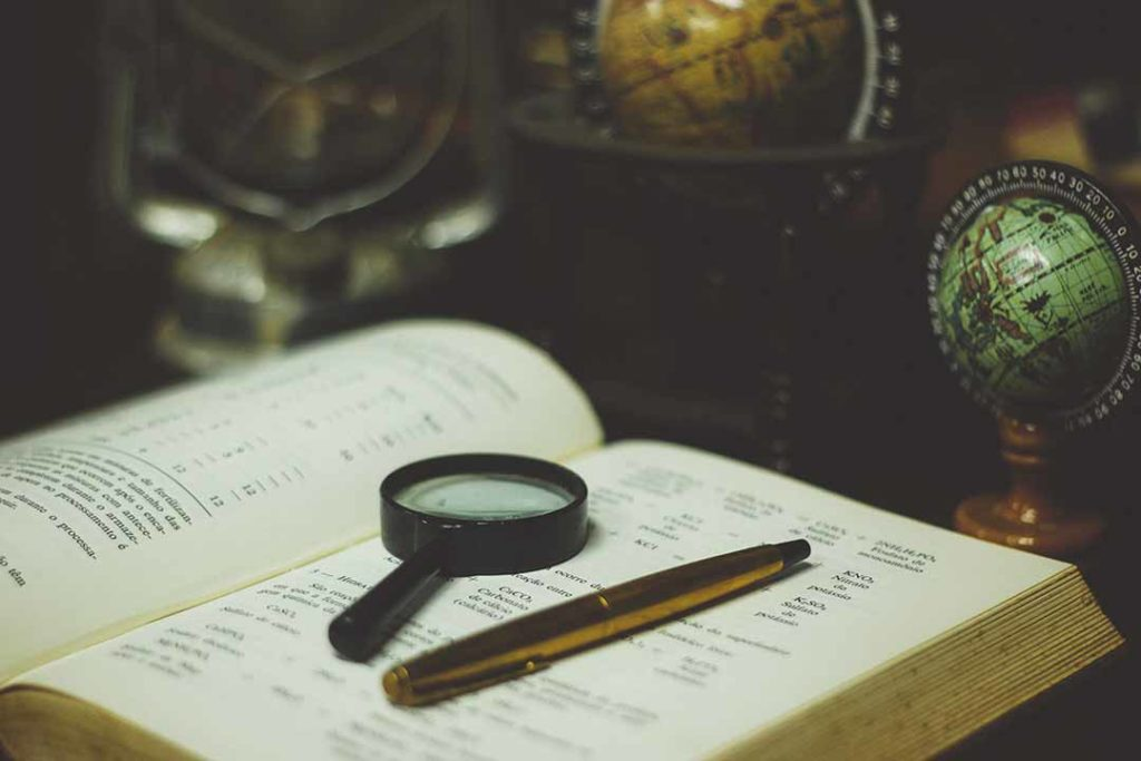 Picture of magnifying glass and pen on book surrounded by globes