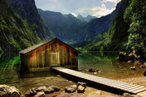 picture of lake in between two mountains with dock and storage house