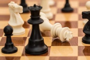 picture of a white king chess piece down on chess board surrounded by black chess pawn, queen, and knight