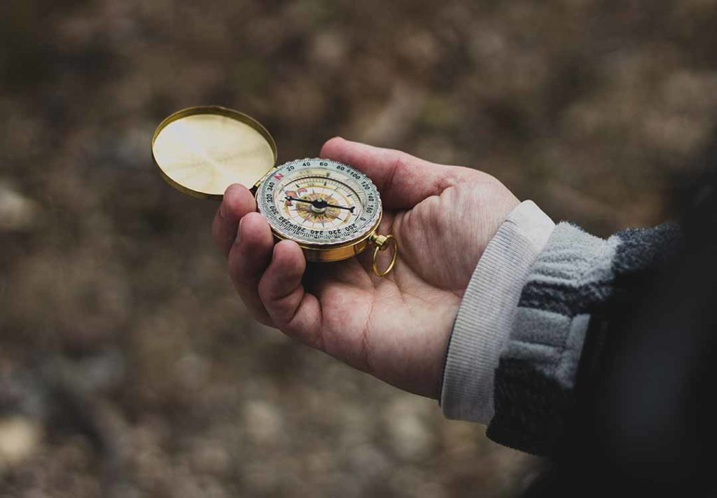 picture of hand holding a gold compass
