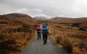 picture of two people walking with backpacks in the wilderness